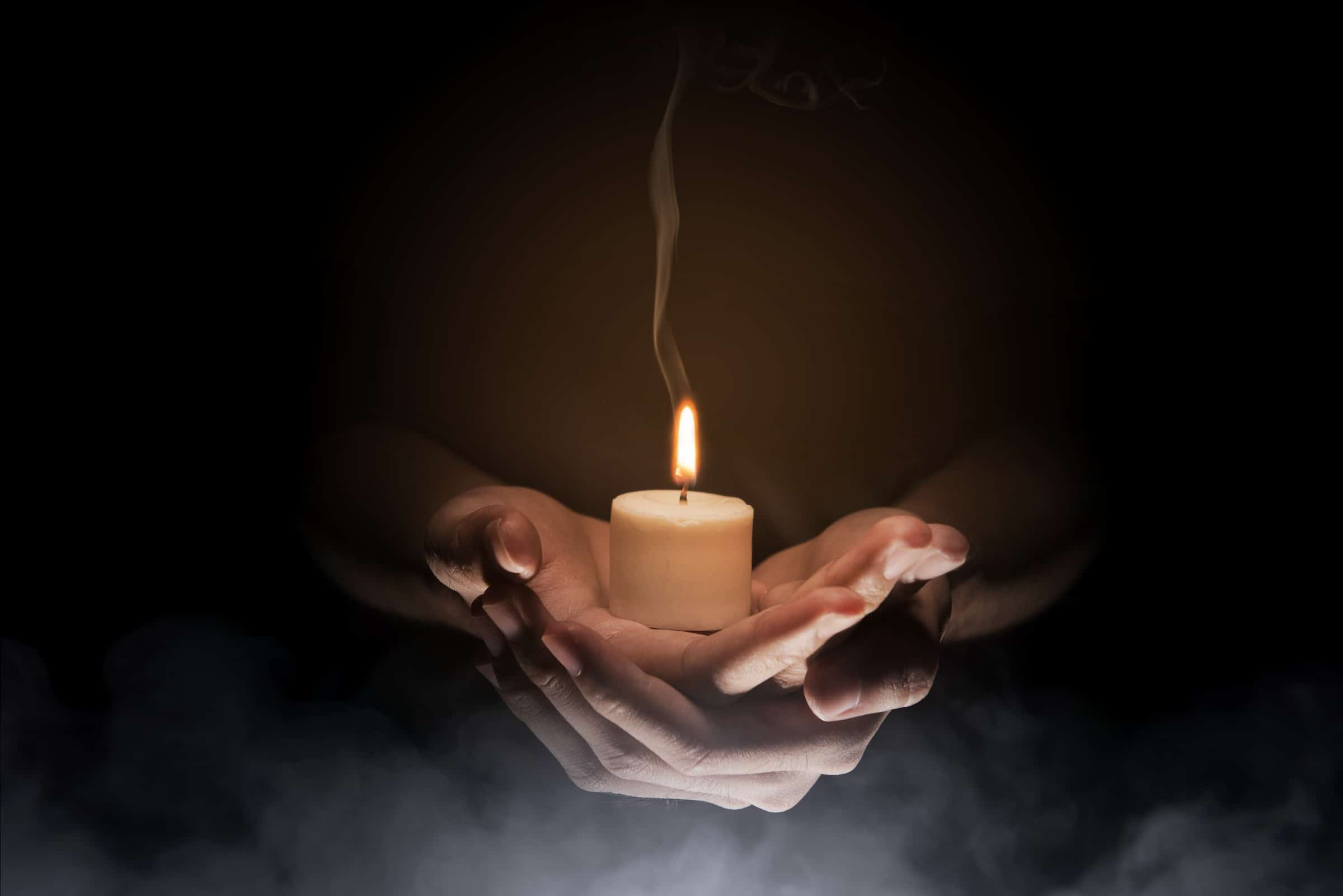 Hands holding candle over dark background. Christian Pray